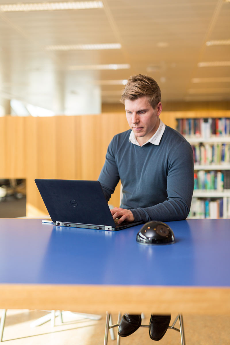 Student in library with laptop